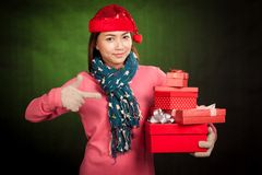 Asian girl with red christmas hat point to gift boxes Stock Photo