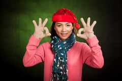 Asian girl with red christmas hat show OK sign Stock Photography
