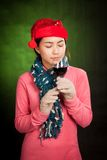 Asian girl with red christmas hat smell wine aroma. On dark green background Royalty Free Stock Photo