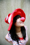 Asian girl with red nose and hat. Asian girl with striped red hat and nose smiling Stock Image