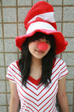 Asian girl with red nose and hat Stock Photo