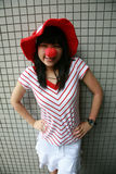 Asian girl with red nose and hat Stock Image
