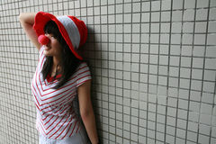Asian girl with red nose and hat. Smiling leaning against a wall Royalty Free Stock Image