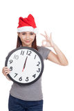 Asian girl with red santa hat and clock show OK sign Royalty Free Stock Images