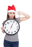 Asian girl with red santa hat and clock show thumbs down Stock Photos