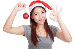 Asian girl with red santa hat hold bauble show OK  and smile Royalty Free Stock Photo