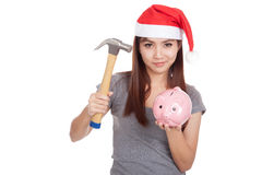Asian girl with red santa hat hold hammer and  pink piggy bank Royalty Free Stock Images