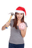 Asian girl with red santa hat hold hammer and  pink piggy bank Stock Images