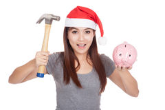 Asian girl with red santa hat hold hammer and  pink piggy bank Stock Photography
