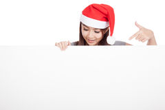 Asian girl with red santa hat look down and point  to a blank si Stock Photos
