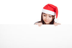 Asian girl with red santa hat look down to a blank sign Stock Photography