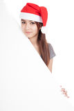 Asian girl with red santa hat with oblique blank sign Stock Photos