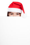 Asian girl with red santa hat peeking behind a blank board Stock Photo