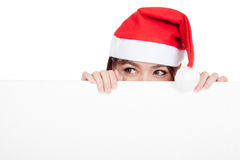 Asian girl with red santa hat peeking behind a blank board Stock Photography
