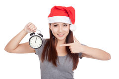 Asian girl with red santa hat point to alarm clock Royalty Free Stock Images