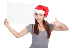 Asian girl with red santa hat point to a blank sign Stock Photo