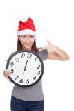 Asian girl with red santa hat point to a clock Royalty Free Stock Photo