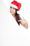 Asian girl with red santa hat point to oblique blank sign Royalty Free Stock Photos