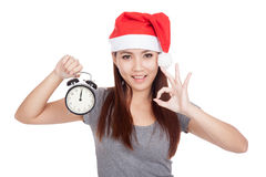 Asian girl with red santa hat show OK with alarm clock Royalty Free Stock Image