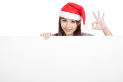 Asian girl with red santa hat show OK with a blank sign Stock Photography