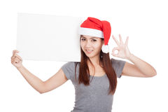 Asian girl with red santa hat show OK with a blank sign Royalty Free Stock Image