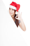 Asian girl with red santa hat show OK with oblique blank sign Royalty Free Stock Images