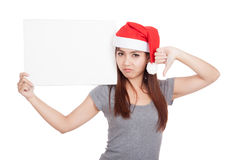 Asian girl with red santa hat thumbs down with a blank sign Royalty Free Stock Photos