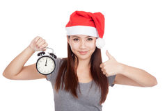 Asian girl with red santa hat thumbs up with alarm clock Stock Images