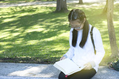 Asian girl relax sit straight leg hold leisure book. Asian girl relax sit hold leisure book in park background royalty free stock photo
