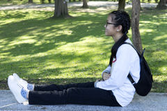 Asian girl relax sit straight leg hold leisure book. In park background stock photo