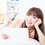 Asian girl relaxed and using tablet Stock Photography