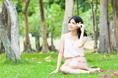 Asian girl relaxing on the grass. Portrait girl sitting on the grass feel relax with flower on her ear Royalty Free Stock Photos