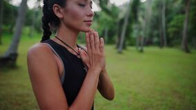 Asian woman meditating in the jungle