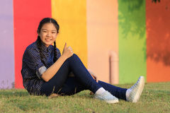 Asian girl relaxing sitting on green grass field of public park Royalty Free Stock Image