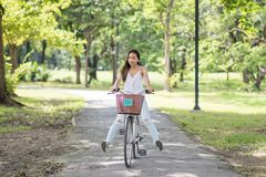 Asian girl ride bicycle in summer park. Asian Beautiful happy  woman riding a bicycle at park and looking at summer garden with sunlight and foliage bokeh Royalty Free Stock Photography