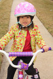 Asian girl riding on bike with helmet stock photo