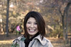 Asian girl with rose. S outdoors on a fall day.  She is of Japanese ethnicity and was 23 at the time of shoot Royalty Free Stock Photography