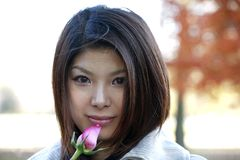 Asian girl with roses. Outdoors on a fall day.  She is of Japanese ethnicity and was 23 at the time of shoot Stock Images
