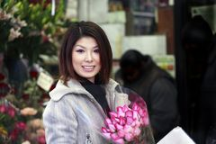 Asian girl with roses. Outdoors on a fall day.  She is of Japanese ethnicity and was 23 at the time of shoot Stock Photo
