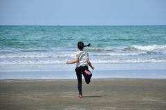 Asian girl is running on the beach into the sea. Excited, sad, disappoint emotions Stock Images