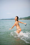 Asian girl running toward water Royalty Free Stock Images
