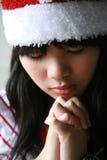 Asian girl with Santa hat. Praying Stock Photo