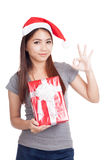Asian girl with santa hat hold gift box show OK sign Stock Photo