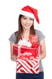 Asian girl with santa hat hold many gift boxes Royalty Free Stock Photos