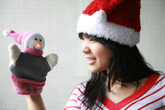 Asian girl with santa hat holding a puppet. Asian girl playing with a christmas puppet Royalty Free Stock Photos