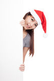 Asian girl with santa hat peeking from behind a blank sign Royalty Free Stock Images