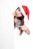 Asian girl with santa hat peeking from behind a blank sign point Stock Photos