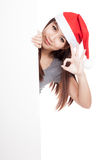 Asian girl with santa hat peeking from behind a blank sign show Stock Photos