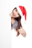 Asian girl with santa hat peeking from behind a blank sign show Royalty Free Stock Image