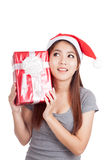 Asian girl with santa hat think what inside a gift box Stock Photography